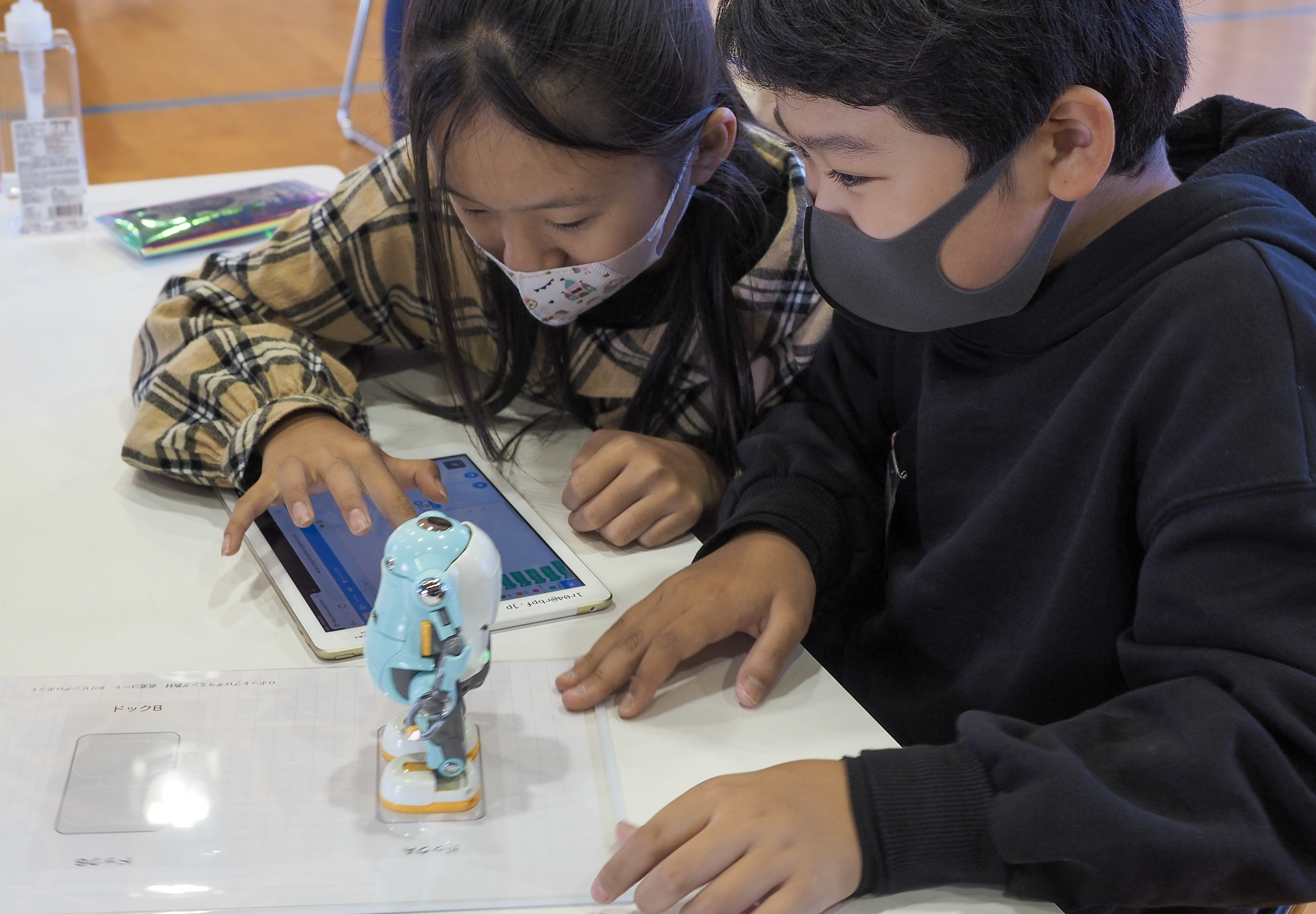 two girls looking into tablet trying to move robot