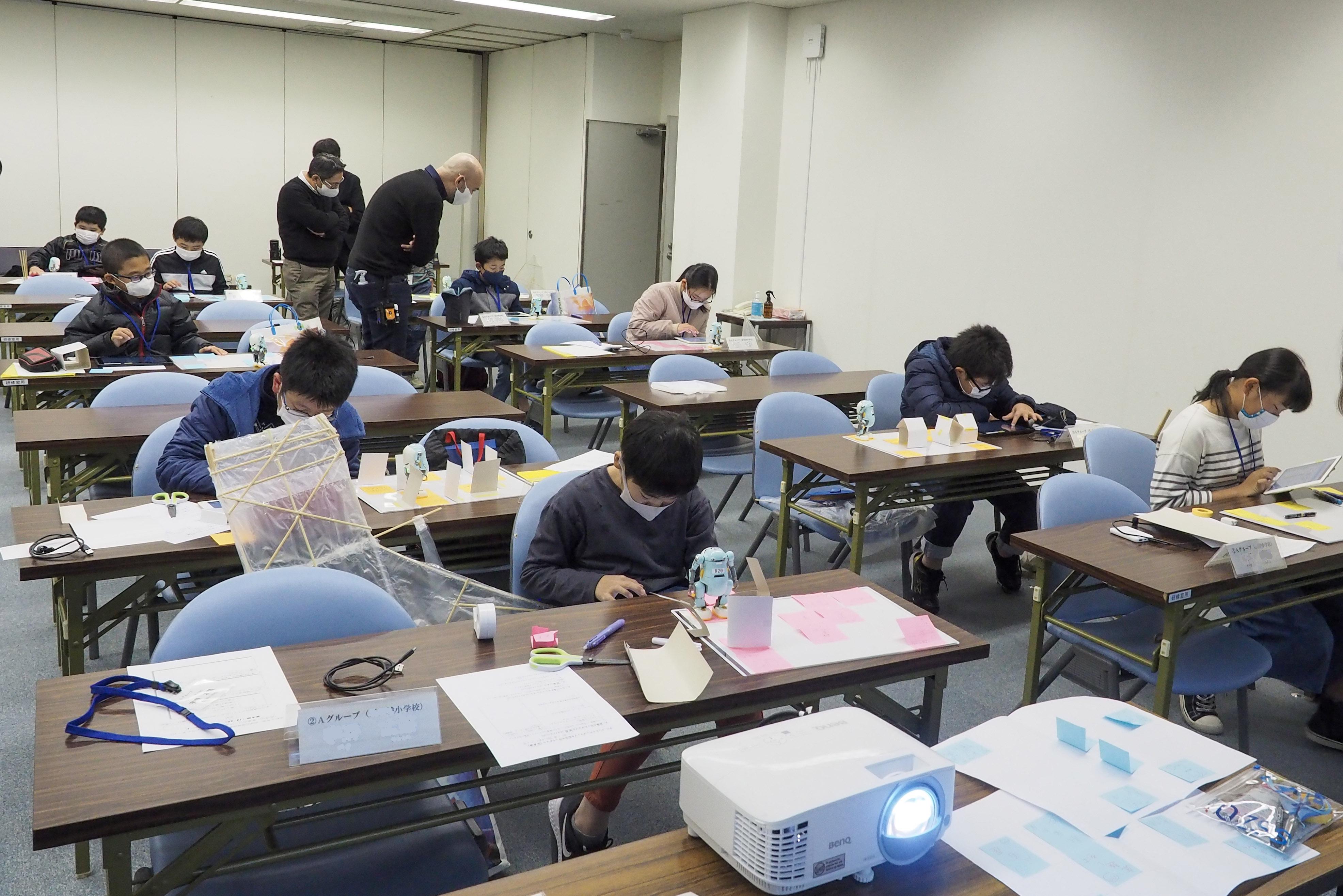 研修室の中で10人ほどの子ども達がタブレットを使ってロボットをマップの上で動かそうとしている。